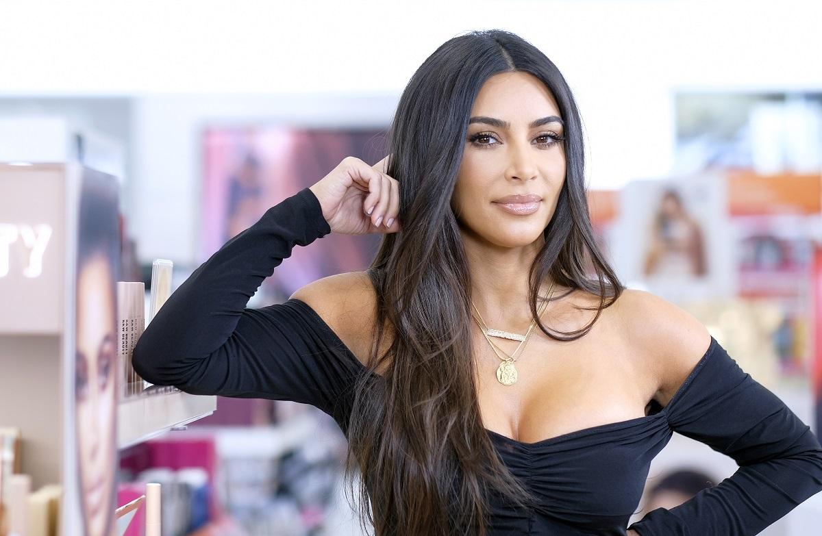 Kim Kardashian la lansarea KKW Beauty în octombrie 2019. Fundal din magazinul Ulta, Kim Kardashian poartă o rochie neagrp, mulată, cu mâneci, decolteu, fără umeri, părul lung