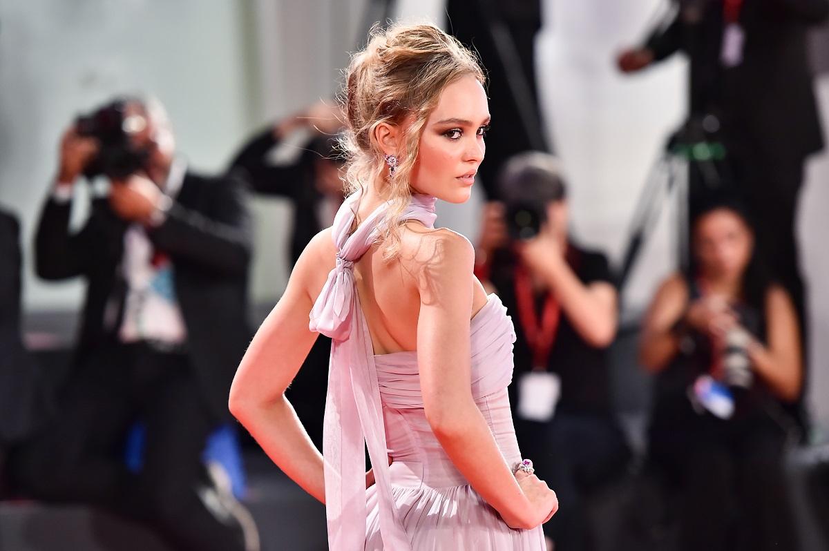 Lily-Rose Depp pe covorul roșu la premiera The King de la Veneția. Îmbrăcată într--o rochie roz, fără bretele, mulată pe torso