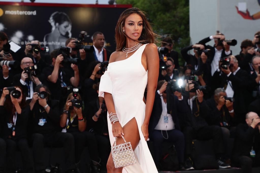 Mădăina Ghenea, într-o rochie albă, lungă, pe covorul roșu, la Venice Film Festival