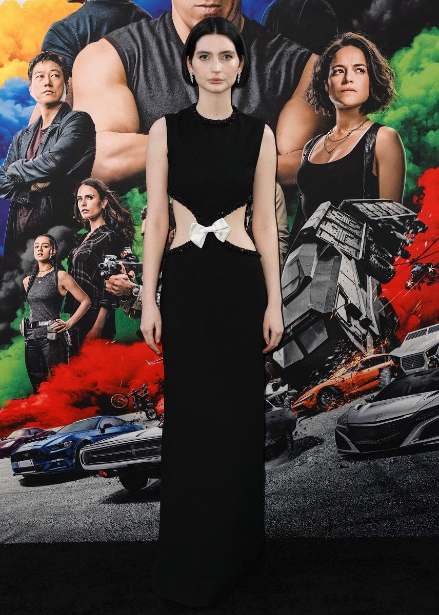 Meadow Walker, fiica lui Paul Walker, la premiera filmului F9, Hollywood, California, pe 18 iunie 2021. A purtat o rochie neagră, cu decupaje în talie și o fundă. Fundal cu posterul din film