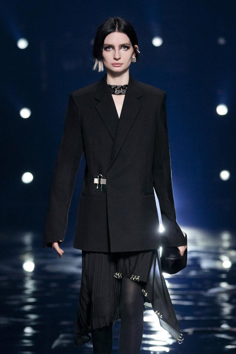 Meadow Walker, fiica lui Paul Walker, pe podiumul Givenchy, de la Săptămâna Modei din Paris, 2021. Îmbrăcată în costum negru, cu pantaloni de culoare neagră, fundal întunecat