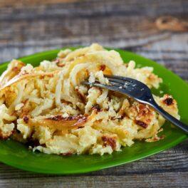 Porție de macaroane cu brânză pe o farfurie verde