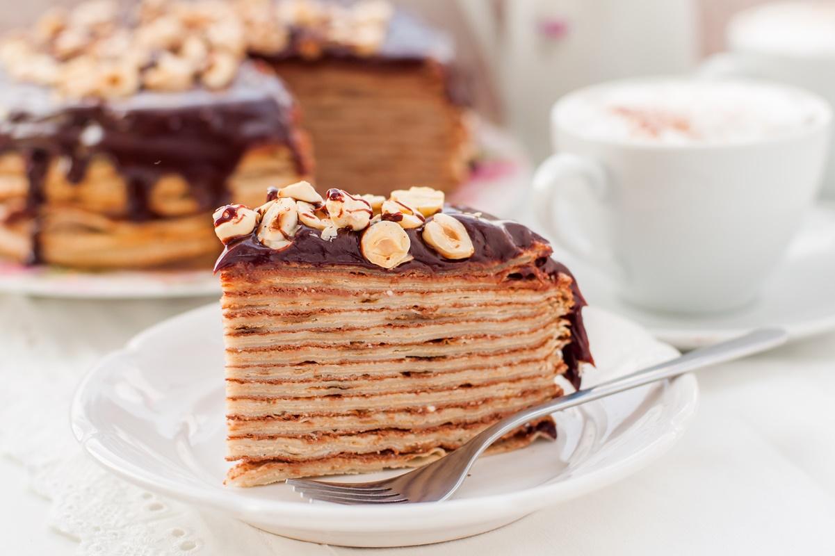 Porție de tort din clătite pe o farfurie albă, în fața platoului cu tort