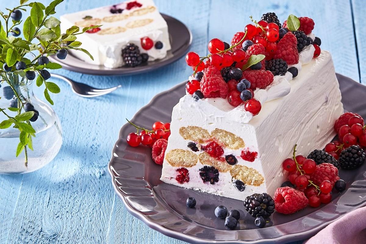 Prăjitură fără coacere cu iaurt și fructe de pădure pe un platou, alături de o porție pe o farfurie