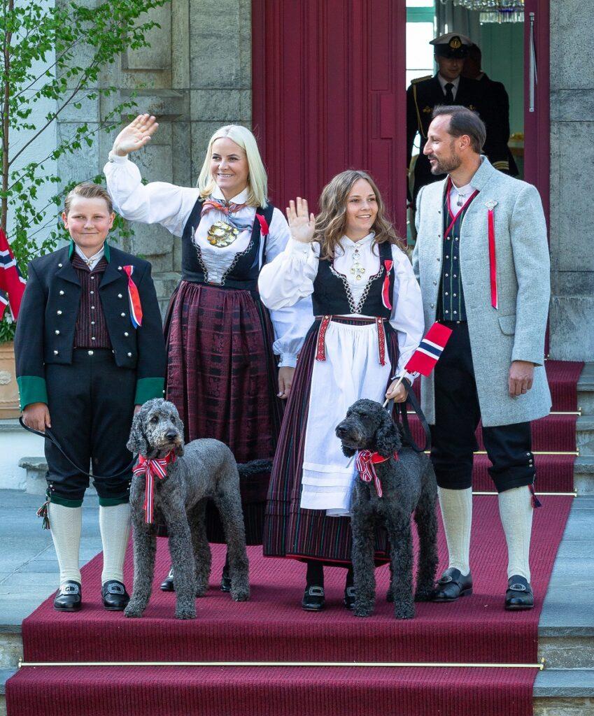 Prințul Haakon alături de familia sa, Mette-Marit, Prințesa Ingrid Alexandra, Prințul Sverre Magnus și câinii familiei, îmbrăcați în port tradițional