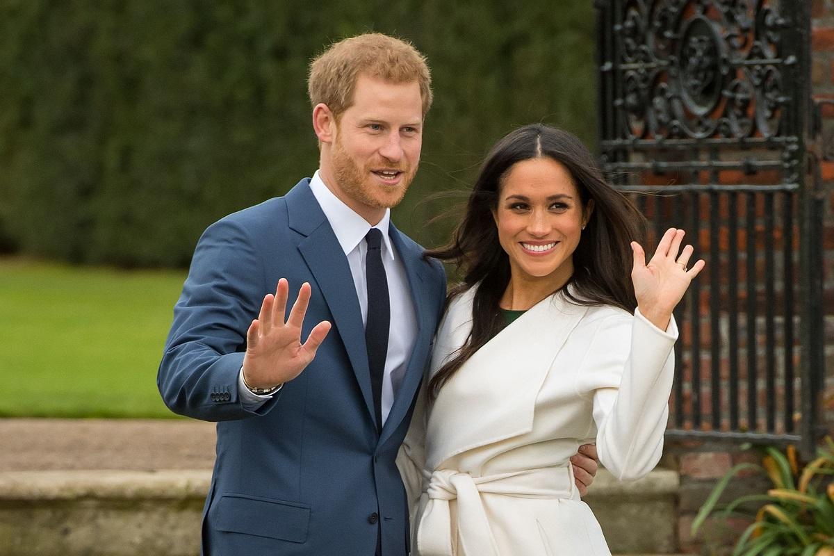Prințul Harry și Meghan Markle, anunțul despre logodnă, noiembrie 2017. El poartă un costum albastru, cu o cravată albastră. Ea poartă un perdesiu alb și are părul desprins. Fundal cu verdeață