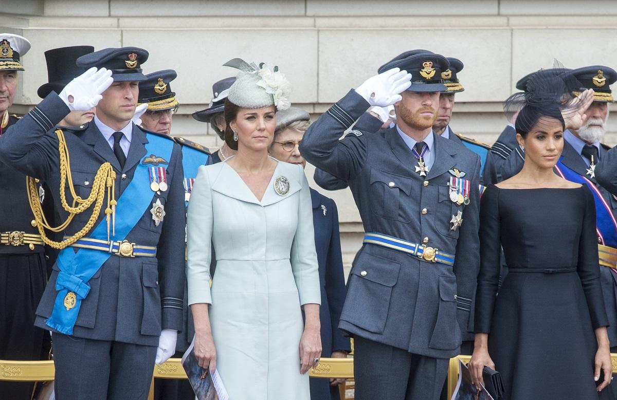 Prințul William, Kate Middleton, Prințul Harry, Meghan Markle au participat împreună la ceremonia RAF 100, de la Buckingham Palace, în anul 2018. Ei au purtat costumele lor albastre, Kate s-a îmbrăcat într-o ținută albastră, Meghan a purtat o ținută neagră