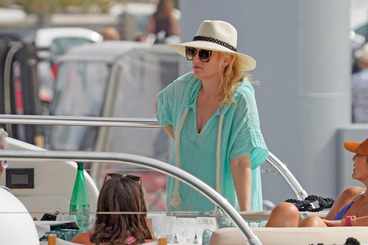 Rebel Wilson, pe o ambarcațiune de lux, în Erupa, îmbrăcată într-un pareo verde, cu pălărie și ochelari de soare