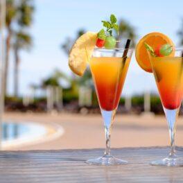 Două pahare de cocktail pe un blat de lemn în fața unei piscine care sunt umplute cu un coktail fără alcool intitulat Cinderella