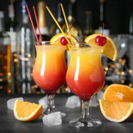 Două pahare care stau pe un bar umplute cu băutura cuddles on the beach lângă care se află bucăți de portocală
