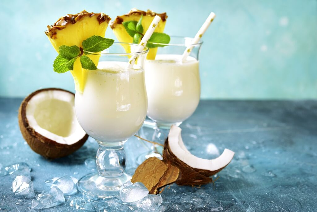 Două pahare pe un blat albastru umplute cu pina colada, un cocktail sofisticat fără alcool, și decorate cu felii de ananas