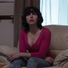 Scarlett Johansson în filmul Under he Skin. Poartă o bluză roz, cu decolteu, are părul negru și stă pe o canapea bej