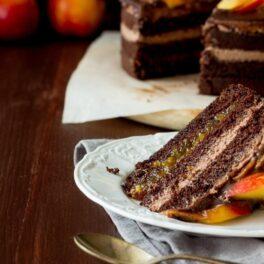 Tort cu nectarine și cremă de ciocolată, porționat pe o farfurie albă.