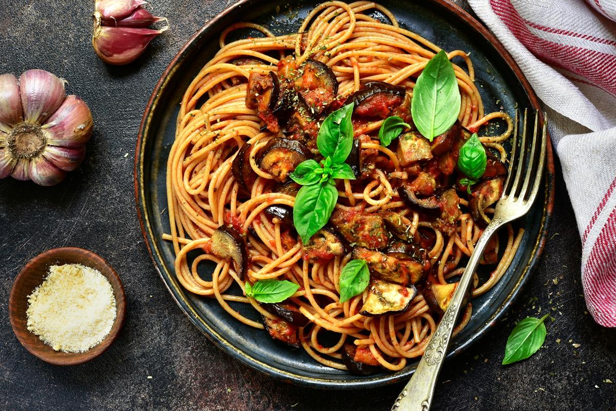 Spaghetti alla Norma într-o tigaie, alături de un bol cu brânză răzuită și usturoi