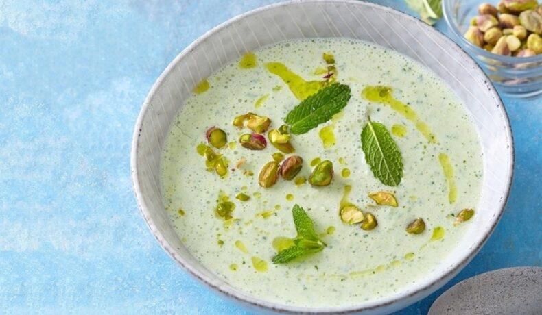 Supă rece de castraveți cu mentă, in bol de servire, decorată cu fistic, mentă și ulei