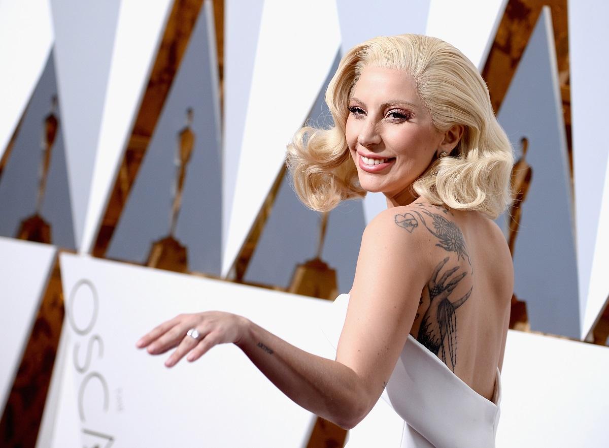 Lady Gaga a apărut la cea de-a 88-a ediție a Premiilor Oscar într-o rochie albă, fără mâneci, ce i-a pus în evidență tatuajele. Ea a purtat părul blond în bucle ușoare, cu fundal cu alb și gri
