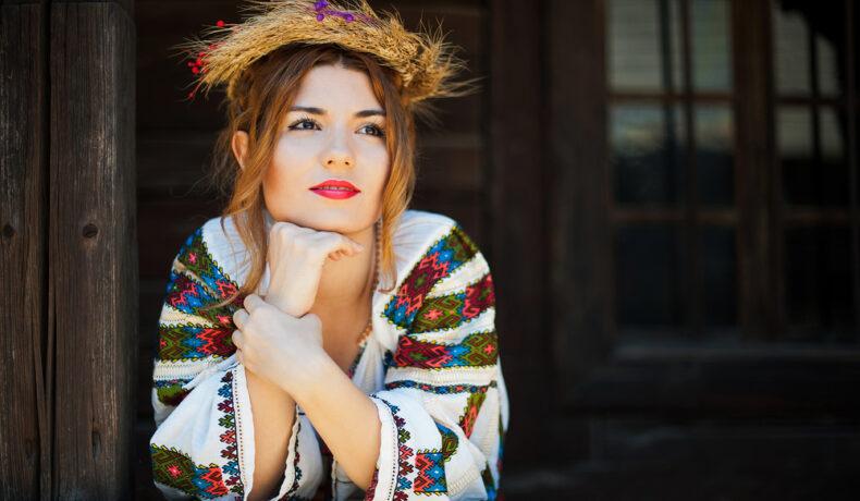 O tânără fată, frumos machiată, cu o coroană din spic de grâu, îmbrăcată în ie