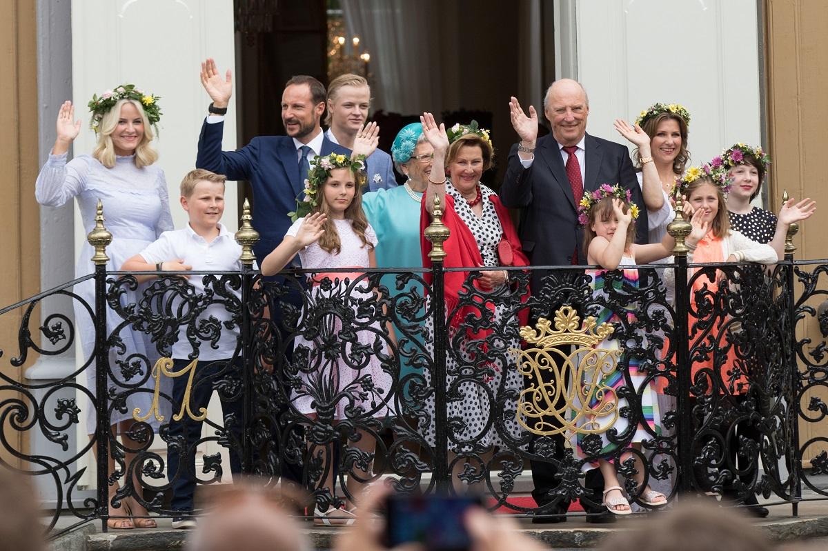 Familia Regală din Norvegia la Royal Silver Jubilee, în 2016. Toți se află pe balcon și fac cu mâna la public. Fetele au coroane de flori și sunt îmbrăcate în alb, în mare parte