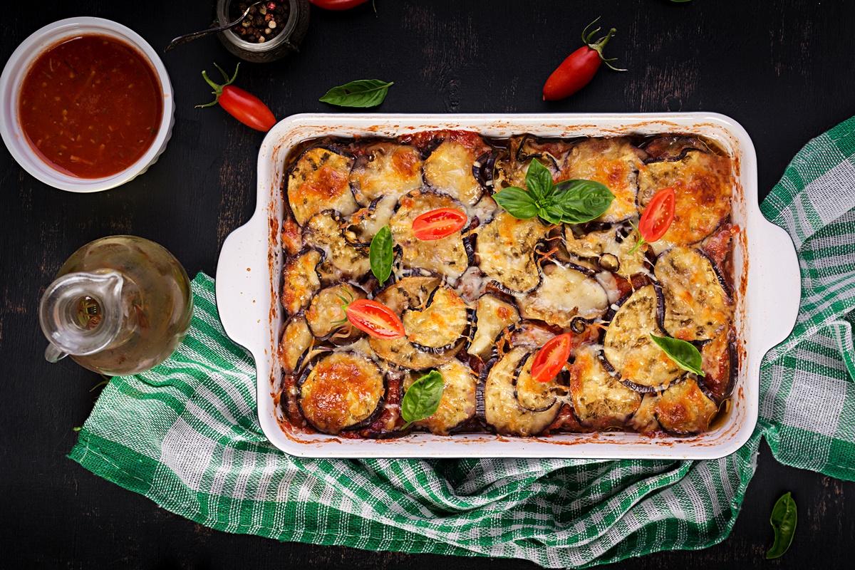 Formă ceramică termorezistentă cu vinete la cuptor cu mozzarela și sos de roșii cu usturoi, pe un ștergar verde