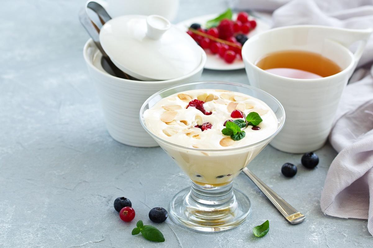 Zabaglione servit în cupă de înghețată, alături de o ceașcă cu ceai și fructe