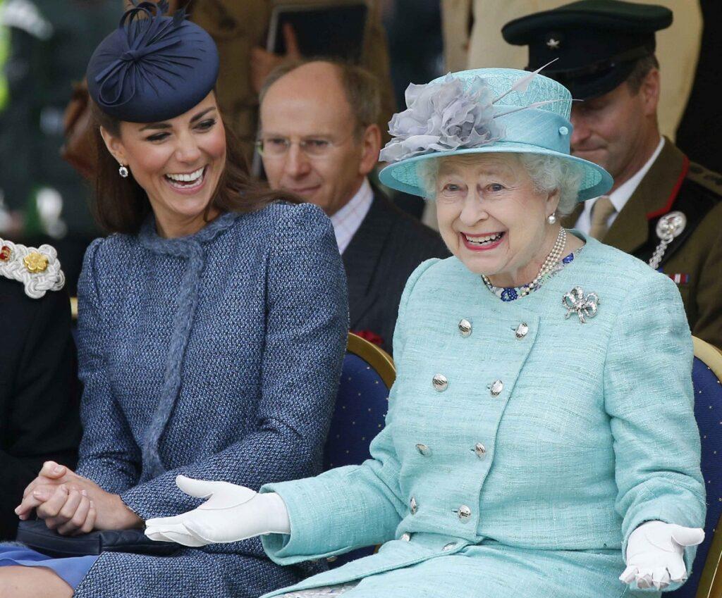 Regina Elisabeta și Kate Middleton, Ducesa de Cambridge, în 2012, în Nottingham. Regina poartă un costum albastru deschis, Kate un costum albastru închis