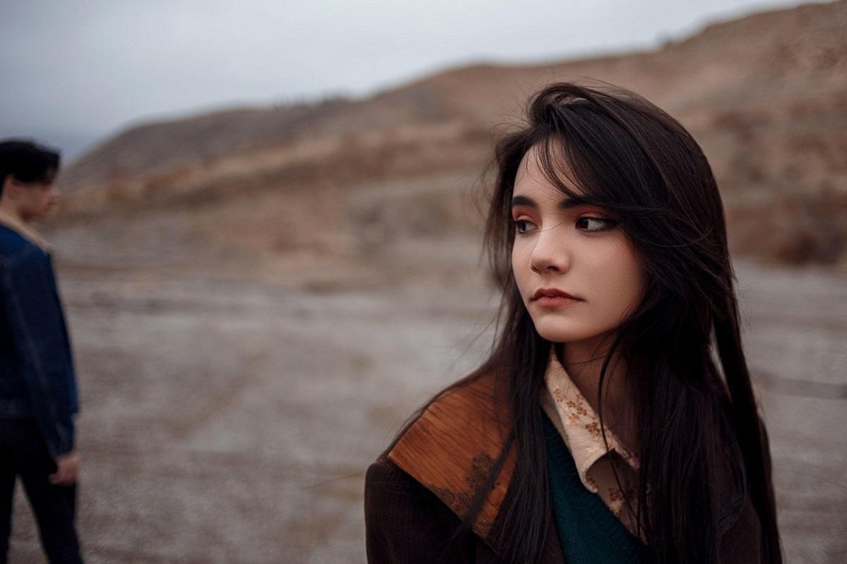O tânără frumoasă care poartă o cămașă maro și privește cu tristețe într-o parte, în timp ce în spate se află un tânăr, care o face să-i fie dor de fostul partener
