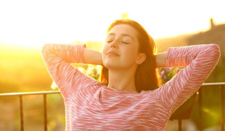 O femeie frumoasă care poartă o bluză roz și stăpe un scaun în timp ce soarele apune în spatele său