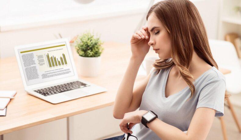 O femeie frumoasă care stă pe un scaun în fața unui birou cu laptp și ține în mână o pereche de ochelari în timp ce cu cealaltă mână își mângâie capul