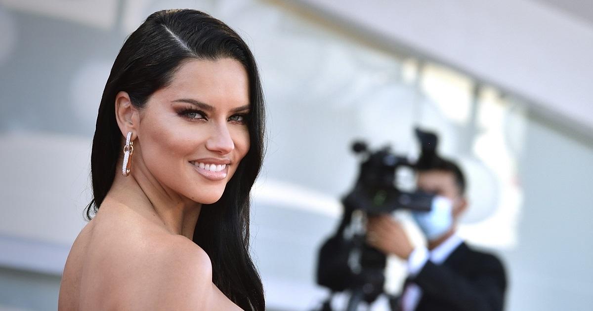 Adriana Lima cu părutl dat într-o parte în timp ce poartă o rochie roșie mulată cu multe paiete