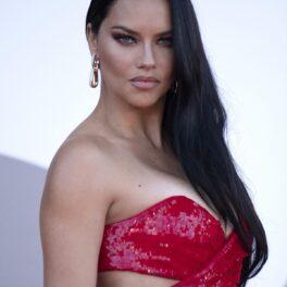 Adriana Lima pe covorul roșu în timp ce poartă o rochie roșie cu paiete și fără bretele