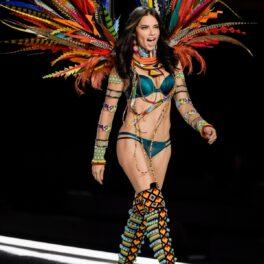 Supermodelul brazilian Adriana Lima în lenjerie intimă albastră cu o pereche de aripi colorate în timp ce defilează pe podium pentru un brand celebru de lenjerie intimă în 2017