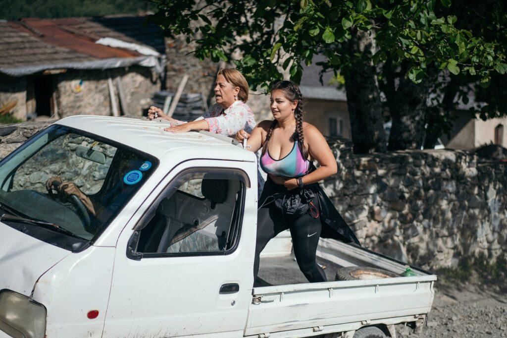 Maria Spernața purtând colanți negri și un tricou gri alături de mama sa, Adriana Trandafir în timp ce se află în remorca unui camion alb la competiția Asia Express: Drumul Împăraților