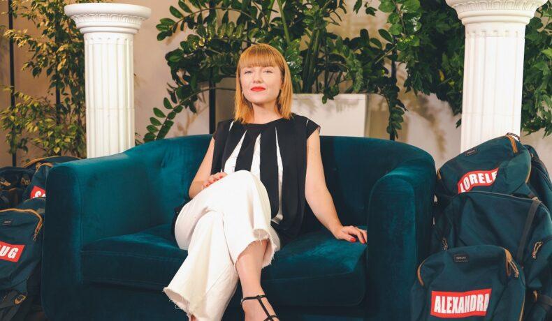 Concurenta de la Asia Express: Drumul Împăraților, Alexandra Ungureanu, în timp ce stă pe o canapea albastră și zâmbește la interviul oferit echipei CaTine.ro
