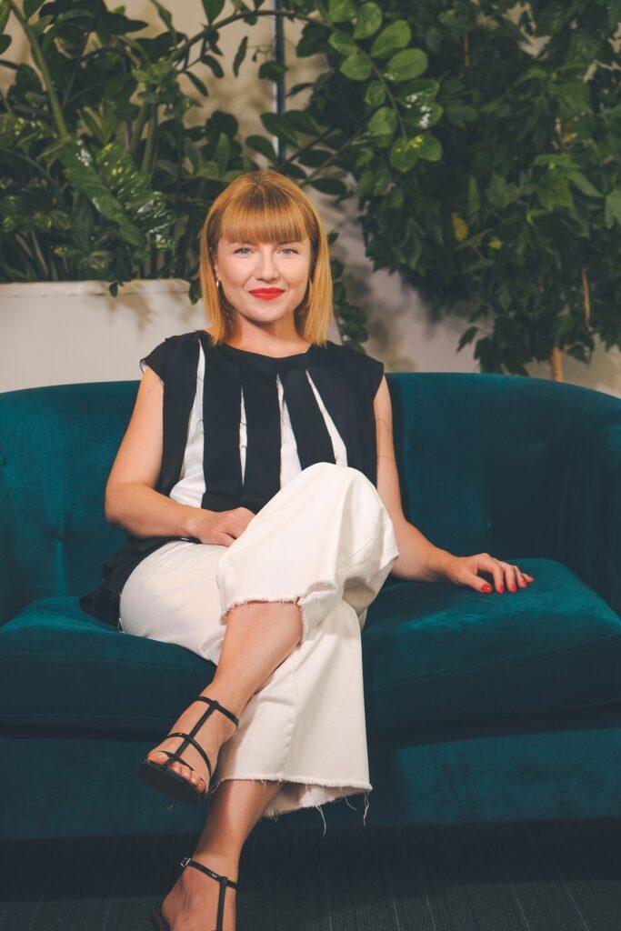 Alexandra Ungureanu în timp ce stă pe o canapea albastră și poartă o pereche de pantaloni albi și o bluză neagră și vorbește despre experiența la Asia Express