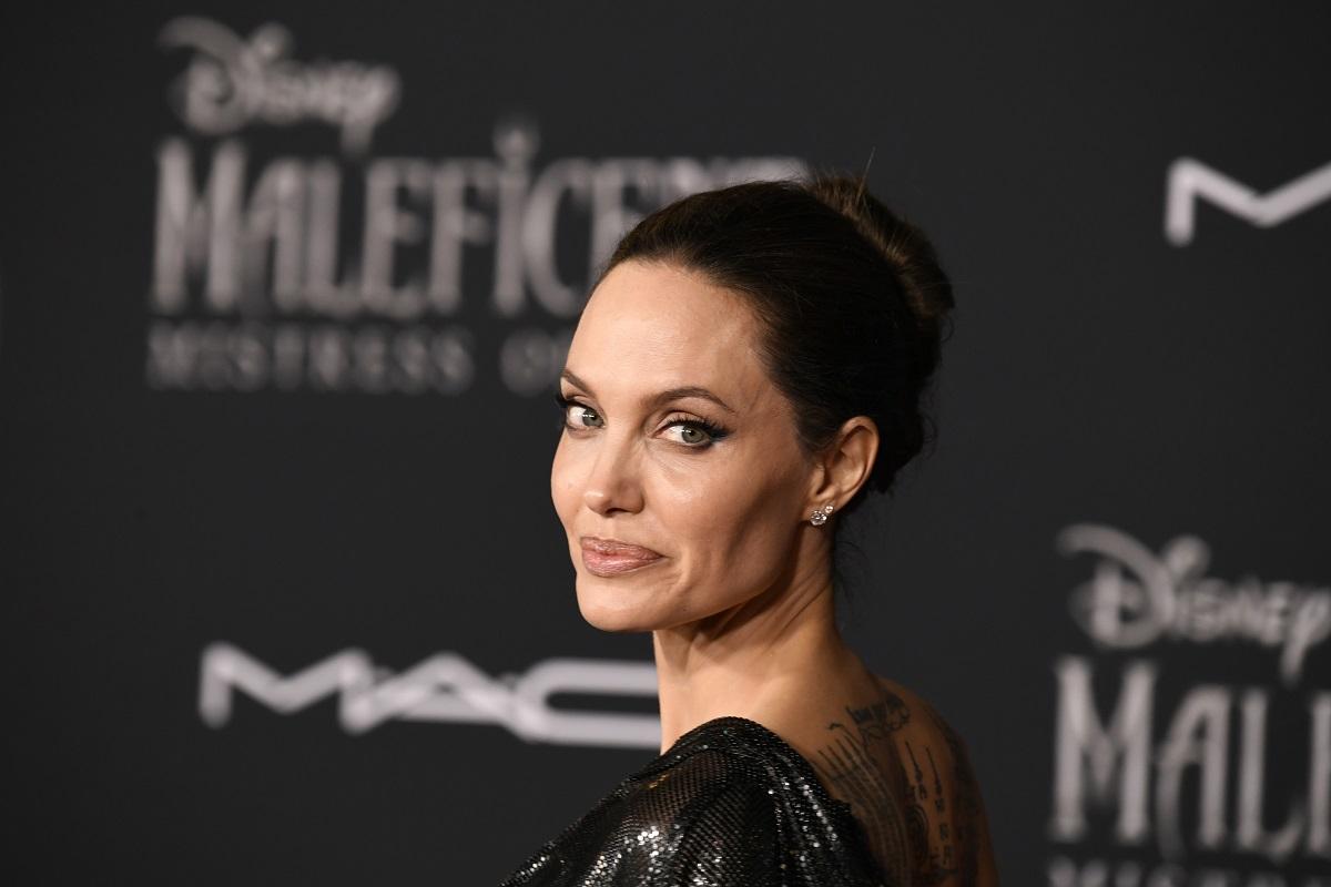 Angelina Jolie într-o rochie neagră în timp ce pozează pe covorul roșu la premiera filmului Maleficent
