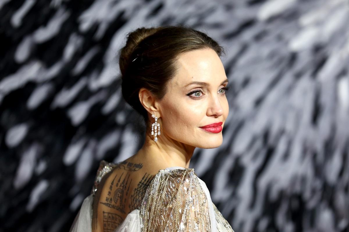 Actrița Angelina Jolie cu părul prins într-un coc pe covorul roșu la premiera filmului Maleficent