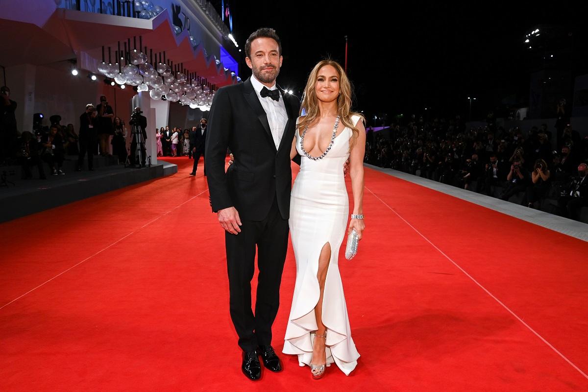 Ben Affleck la costum negru pe covorul roșu, alături de Jennifer Lopez care poartă o rochie albă mulată în timp ce participă la Festivalul de Film de la Veneția 2021 la premiera filmului The Last Duel