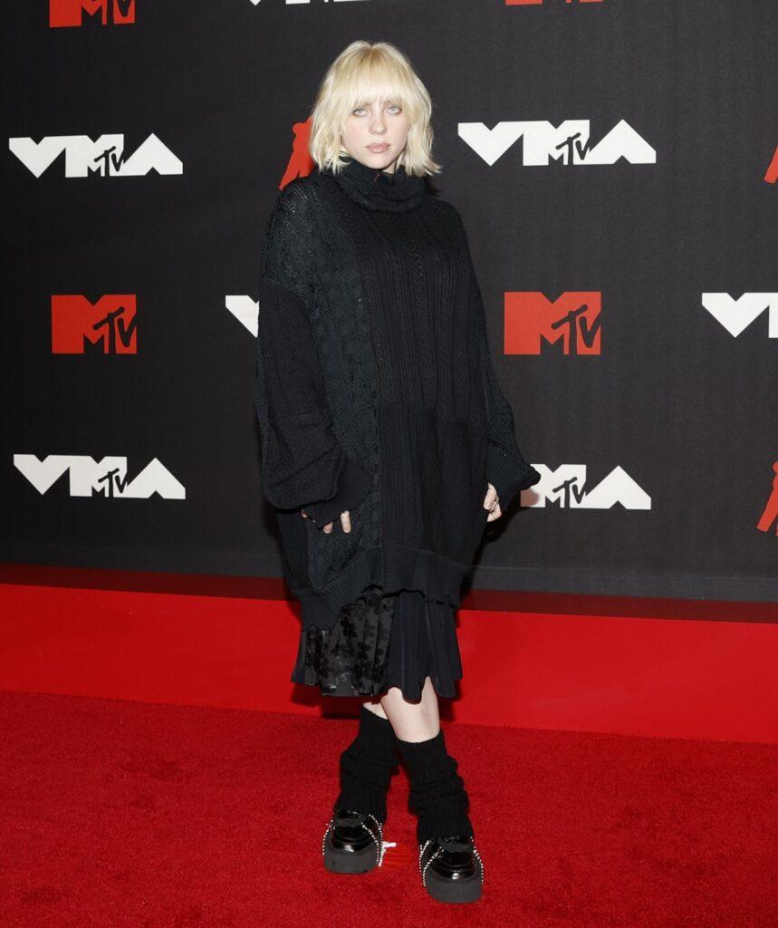 Artista Billie Eilish într-o fustă neagră acoperită cu un pulover tricotat negru, pe covorul roșu, la ținutele extravagante de la MTV VMA 2021
