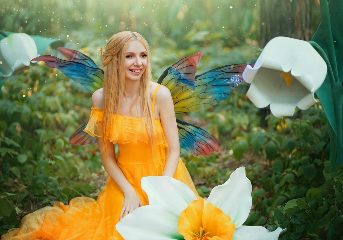 O femeie frumoasă care poartă o rochie galbenă și stă printre flori albe în timp ce se gândește la cele mai active zodii