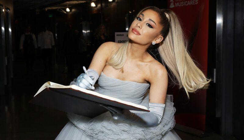 Ariana Grande într-o rochie gri în timp ce semnează un album și se află pe lista cu cele mai bogate vedete care au sub 30 de ani