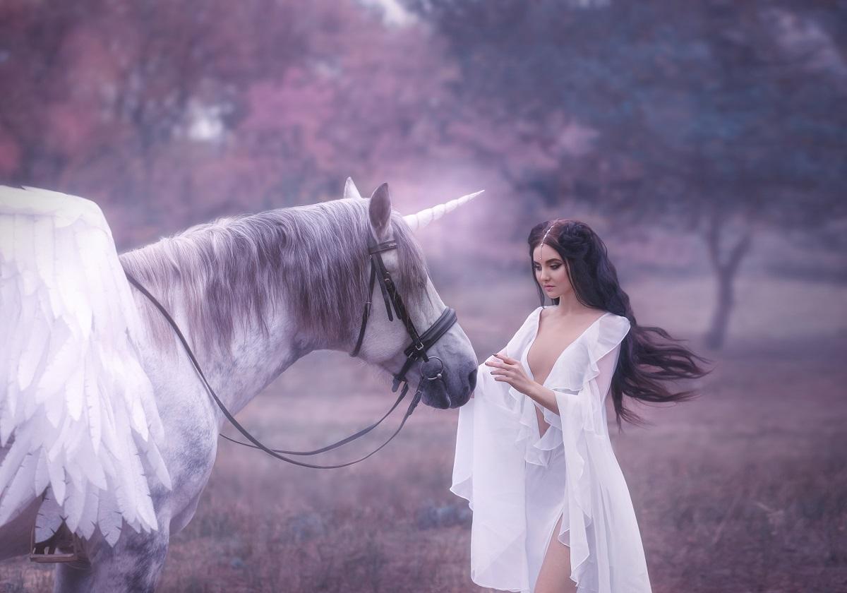 O femeie frumoasă într-o rochie albă care se numără printre cele mai rare zodii, în timp ce mângâie pe frunte un inorog