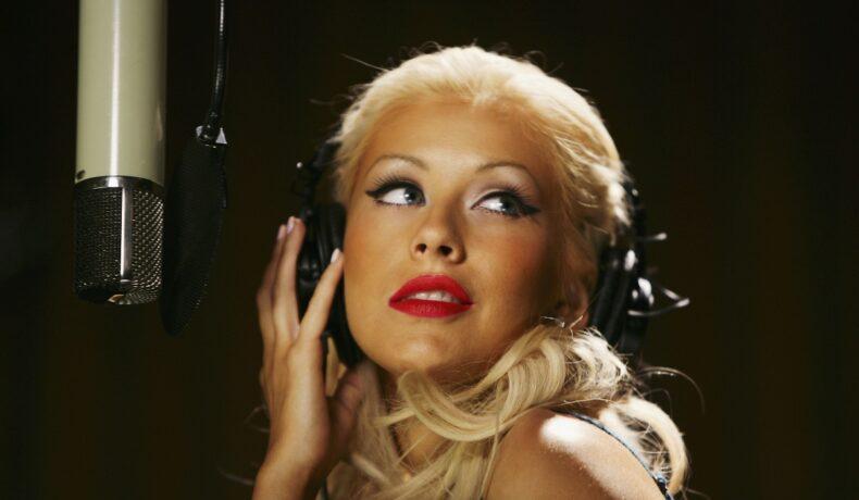 Portret al Christinei Aguilera în timp ce poartă căști și se află în fața unui microfon după ce recent a recreat coperta unui album pe care l-a lansat în 2002