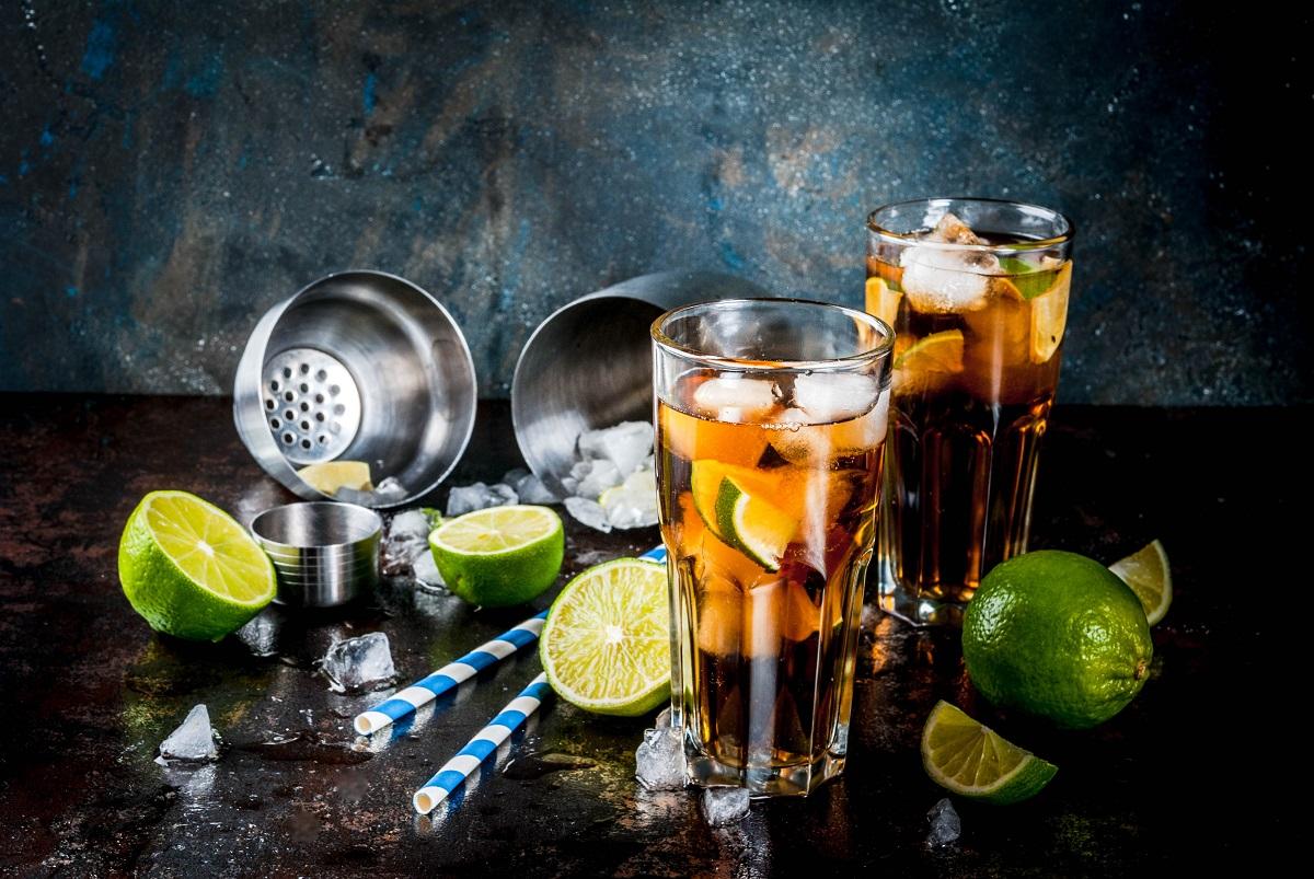 Un blat de lemn negru pe care se află un shaker, cuburi de gheață, jumătăți de lime și două paie alături de două pahare pline cu cocktail long island iced