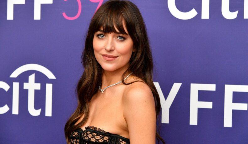 Dakota Johnson cu părul dat pe spate în timp ce pozează pe covorul roșu la Festivalul de Film de la New York 2021