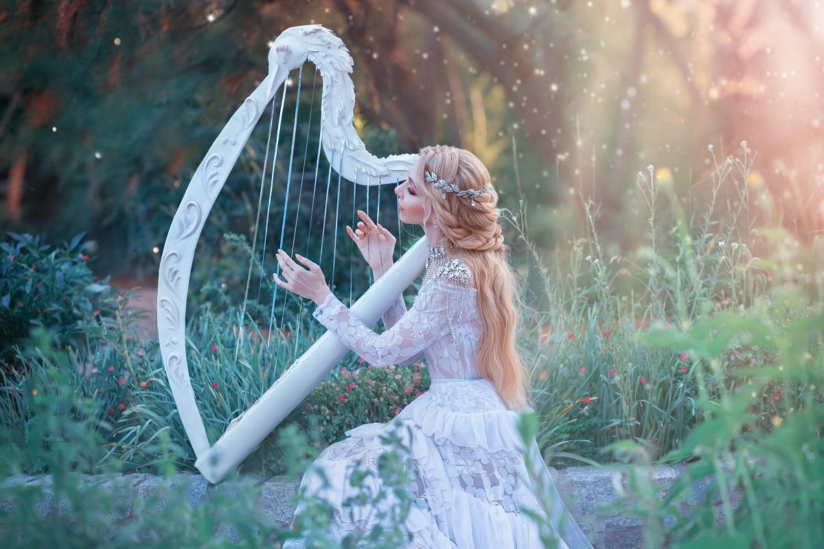 O femeie frumoasă care poartă o rochie albă și se folosește de talentul său ascuns pentru a cânta la harpă