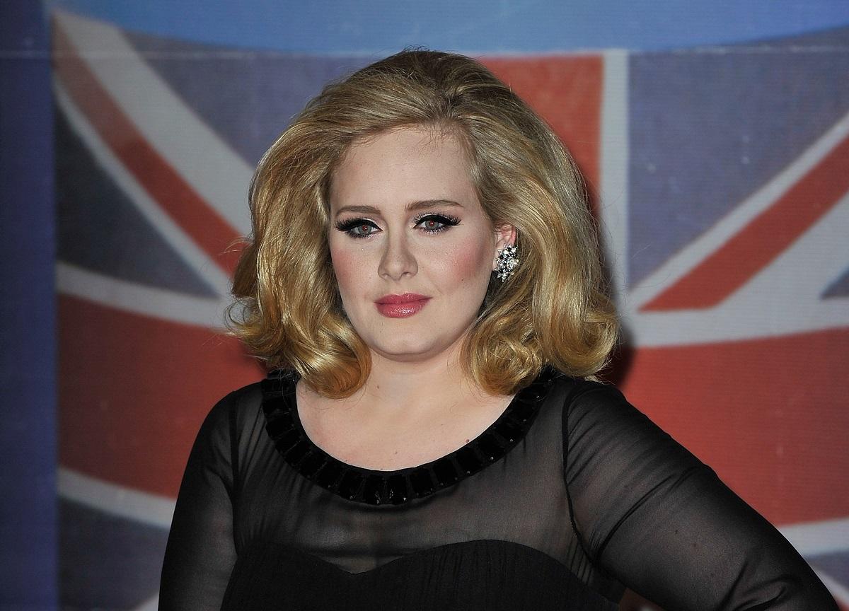 Portret al vedetei Adele care paortă o bluză neagră cu mâneci transparente în timp ce pozează la the brit awards 2012
