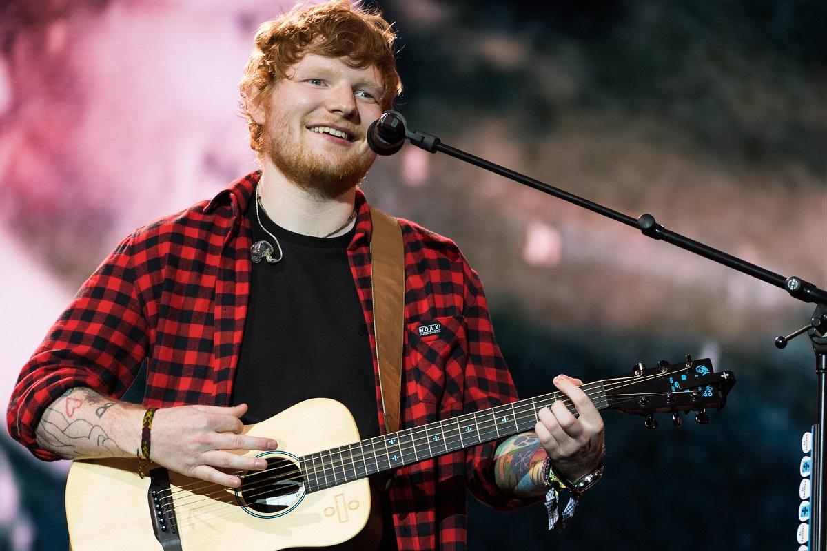 Ed Sheeran pe scenă purtând un tricou negru și o cămașă roșie în carouri în timp ce cântă la microfon în timpul unui concert