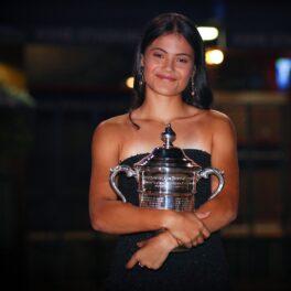 Emma Răducanu într-o rochie neagră, cu trofeul US Open 2021 în brațe