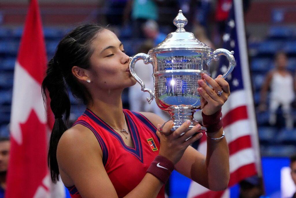 Emma Răducanu care a câștigat US Open 2021 în timp ce sărută trofeul pe terenul de tenis