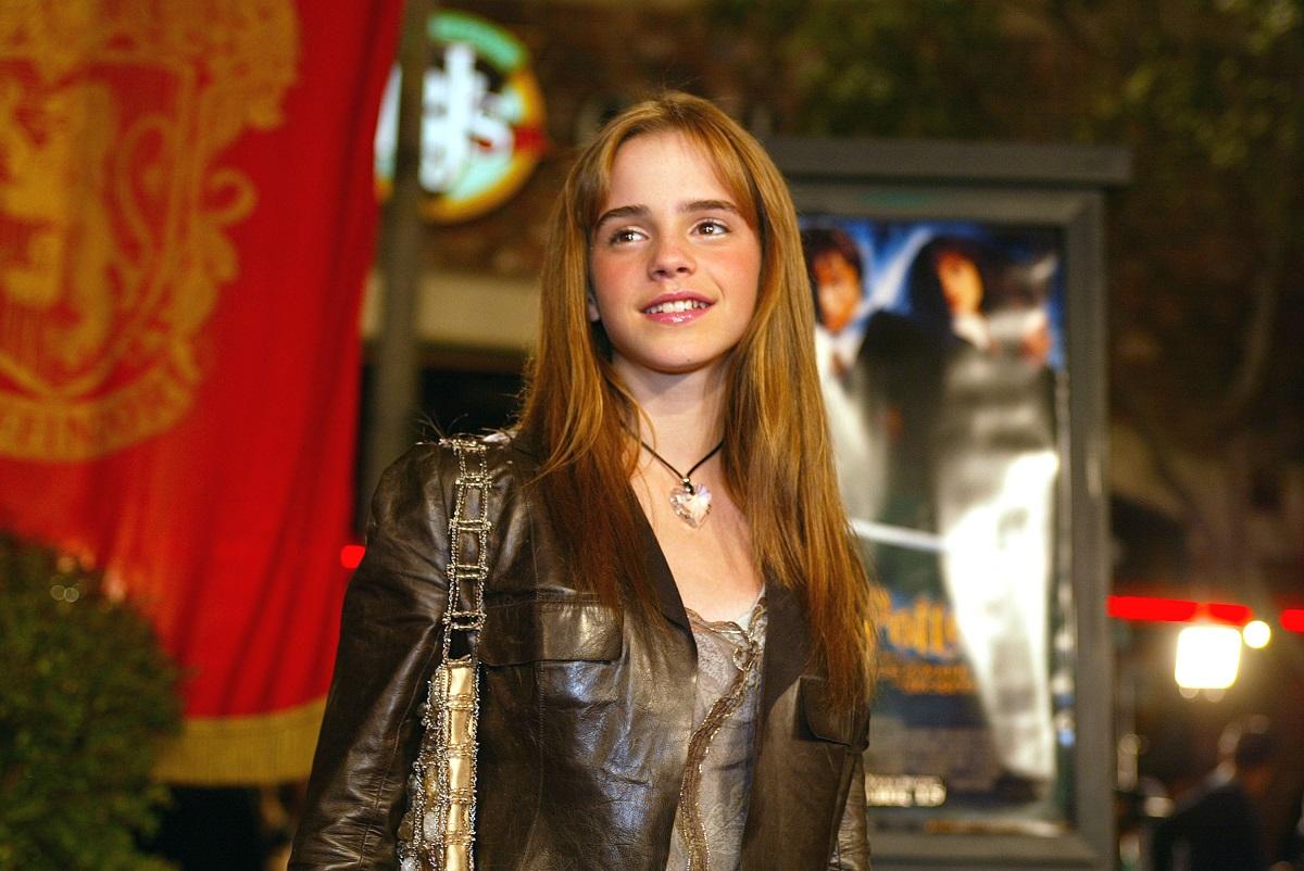 Emma Watson cu părul lung purtând o jachetă maro la premiera filmelor Harry Potter